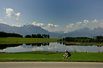 Cyclist passing Forggensee lake close to Neuschwansein castle. Bavaria, South Germany.
