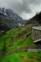 Alpine fencing in spring meadows against the background of the mountains and church. Pitztal valley, Imst district, Austria.