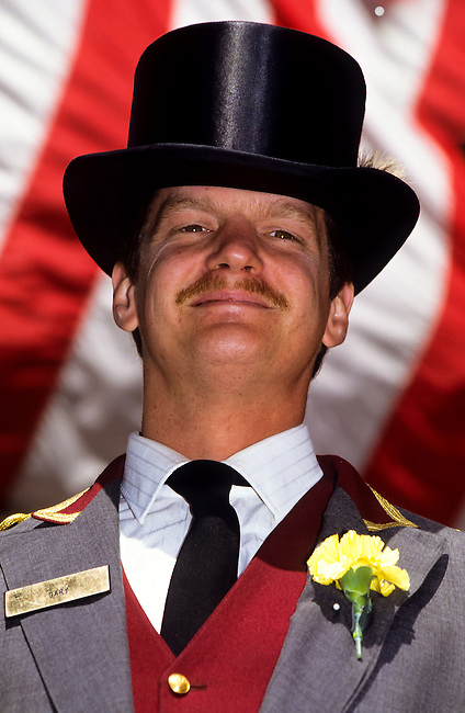 Portrait of a young man in smoking uniforn and with a black bowlerhat in front of Stars and Stripes flag in New York City, USA
