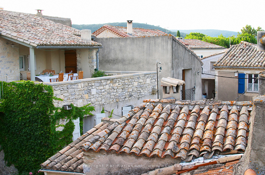Dinner table set on the terrace a summer evening. Chateau de Lascaux, Vacquieres village. Pic St Loup. Languedoc. Village roof tops with tiles.. France. Europe.