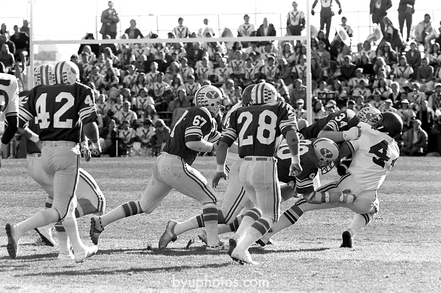 FTB 80 A-28<br /> <br /> BYU vs BYU- University of Utah. 42 Reed Brown or Dana Wilgar. 28 Terry Baker or Mike Russell. 57 Craig Christensen. 34 Phil Jensen.<br /> <br /> November 23, 1974<br /> <br /> Box: 6373<br /> <br /> Photography by: Mark Philbrick/BYU<br /> <br /> Copyright BYU PHOTO 2008<br /> All Rights Reserved<br /> 801-422-7322<br /> photo@byu.edu