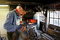 Nederland Broek op Langedijk 2015. Museum BroekerVeiling. De oudste doorvaarveiling ter wereld. Hier werd in vroeger tijden groente geveild. Smid aan het werk in de smederij