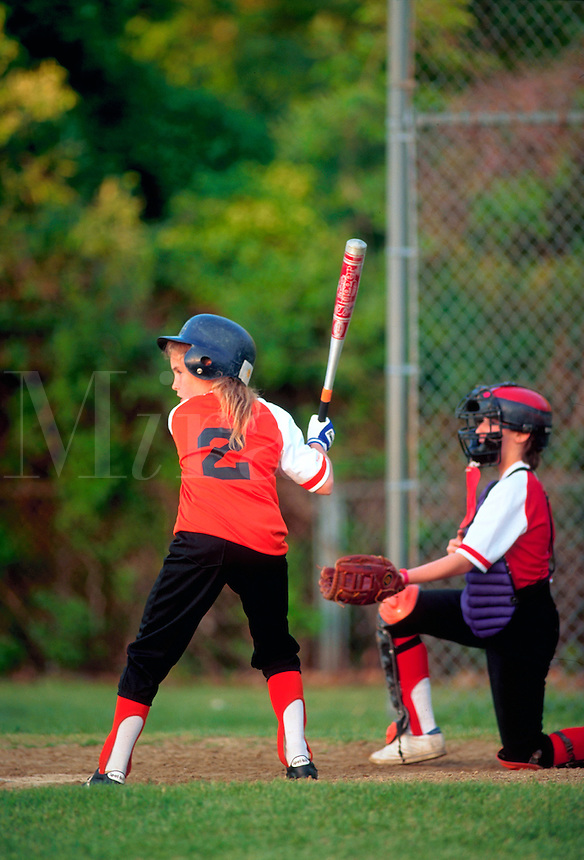 A young female baseball player at bat during a youth recreational Little League game.