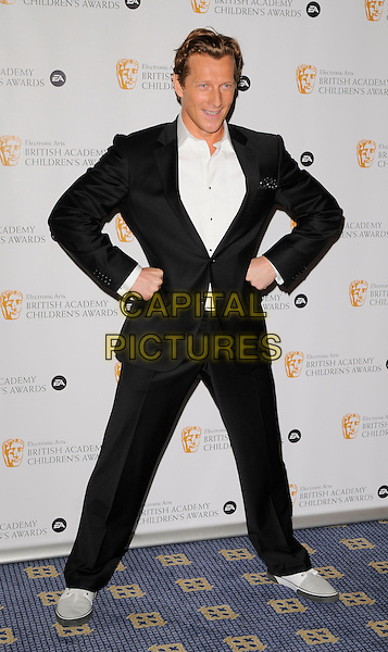 MAGNUS SCHEVING.Pressroom at the The British Academy Children's Film and Television Awards, London, Hilton Hotel, Park Lane, London, England..November 30th, 2008.BAFTA BAFTA's press room full length black suit white shirt hands on hips .CAP/CAN.©Can Nguyen/Capital Pictures.