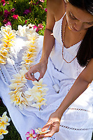 Beautiful Hawaiian woman making a fragrant plumeria lei on the lawn