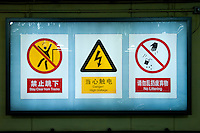 Underground landscape view of back lit subway safety signage at a B?ij?ng dìti?zhàn in D?ngchéng Q? in Beijing.  © LAN