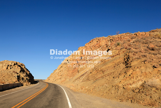Rural highway running through rugged terrain near Elephant Butte in New Mexico, USA.