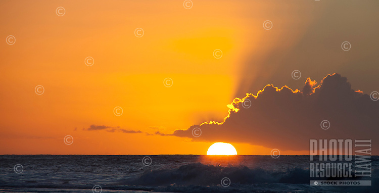 The setting sun turning the sky gold off Ke'e Beach, near Na Pali, Kauai.