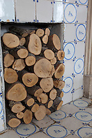 Logs are stored in a fireplace decorated with blue and white Dutch style ceramic tiles in Whitehouse, a guest house in Chillington, Devon