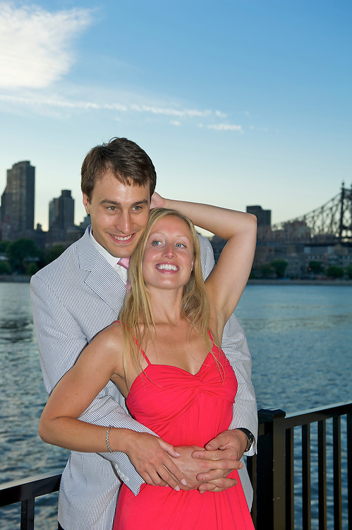 Playful shot of engaged couple with The East River and Queensborough Bridge in the background.