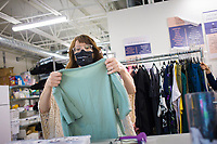 Kim Vetter, volunteer coordinator, shows volunteers how to sort clothes for sale, Friday, July 31, 2020 at Beautiful Lives Boutique in Bentonville. Volunteers from the Bentonville Discipleship group gave their time to help tag and sort clothes for the boutique. Beautiful Lives is a nonprofit that raises money to help women impacted by a variety of situations from homelessness and incarceration to international issues like sexual exploitation and trafficking. The boutique donated $4,000 in July to six local charities and four international non-profits that are working to support women said Melissa Rhodes Carter, the executive director for Beautiful Lives's three locations. All of the revenue from the boutiques minus expenses is donated to support women's causes. Check out nwaonline.com/200801Daily/ for today's photo gallery. <br /> (NWA Democrat-Gazette/Charlie Kaijo)