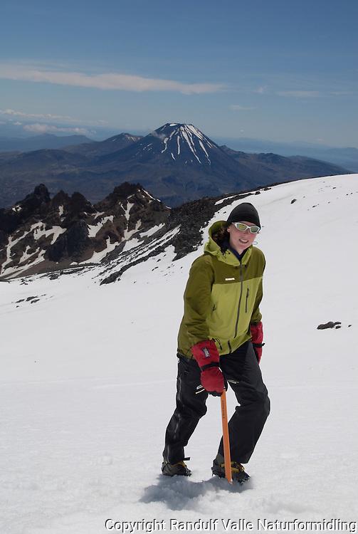 Jente på vei opp Mt Ruapehu. Mt Ngauruhoe i bakgrunnen ---- Girl climbing the slopes ov Mt Ruapehu. Mt Ngauruhoe in the background