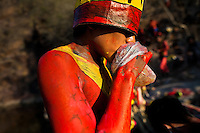"A Cora Indian boy, with body painted all over in red color, inhales the color solvent to get high before the religious ritual ceremony of Semana Santa (Holy Week) in Jesús María, Nayarit, Mexico, 22 April 2011. The annual week-long Easter festivity (called ""La Judea""), performed in the rugged mountain country of Sierra del Nayar, merges indigenous tradition (agricultural cycle and the regeneration of life worshipping) and animistic beliefs with the Christian dogma. Each year in the spring, the Cora villages are taken over by hundreds of wildly running men. Painted all over their semi-naked bodies, fighting ritual battles with wooden swords and dancing crazily, they perform demons (the evil) that metaphorically chase Jesus Christ, kill him, but finally fail due to his resurrection. La Judea, the Holy Week sacred spectacle, represents the most truthful expression of the Coras' culture, religiosity and identity."