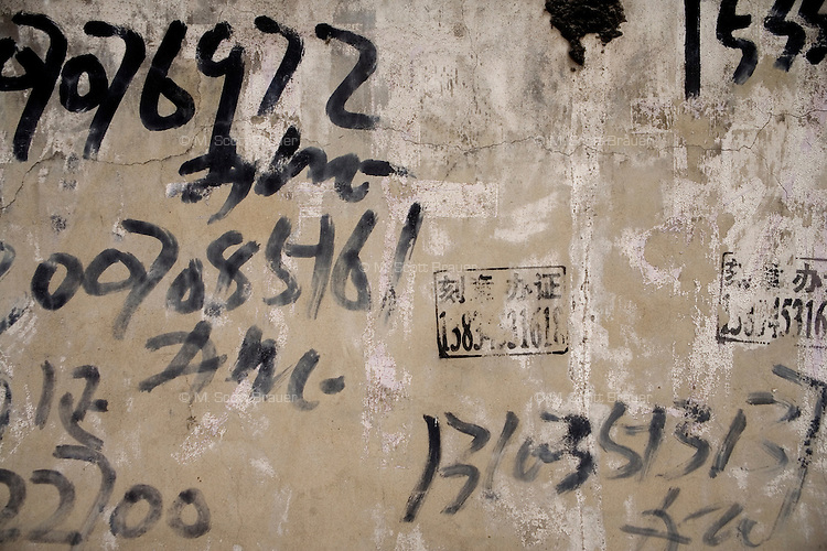 Laborers numbers are painted on a wall in Pingyao, Shanxi, China.