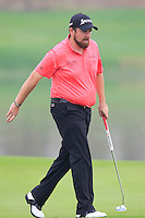 Shane Lowry (IRL) taps in for birdie on the 11th green during Friday's Round 2 of the 2014 BMW Masters held at Lake Malaren, Shanghai, China 31st October 2014.<br /> Picture: Eoin Clarke www.golffile.ie