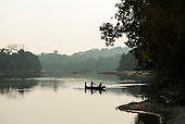 Aldeia Baú, Amazon,  Para State, Brazil. Kayapo children take a canoe across the river at dusk.