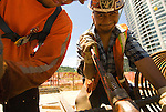 Workers installing rebar, high rise building construction