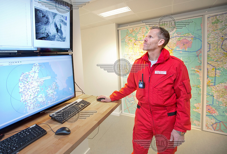 Pilot Jan Nielsen checks the weather in the OPS -room. Denmarks first  air ambulance serivce, operated by Norwegian Air Ambulance. The crew is pilot Jan Nielsen, HEMS paramedic Lars Greve-Wilms and doctor Rikke Helene Rasmussen. <br /> <br /> The crew operate an Airbus EC-135 out of the Ringsted base, one of three bases in Denmark.