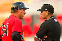 Hickory Crawdads manager Bill Richardson #24 argues a call at first base with umpire Roberto Ortiz during the game against the Greenville Drive at L.P. Frans Stadium on September 3, 2011 in Hickory, North Carolina.  The Crawdads defeated the Drive 3-0.  (Brian Westerholt / Four Seam Images)