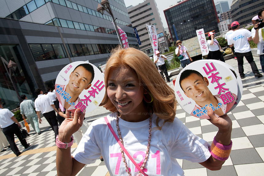 A young female volunteer holds fans printed with the face of actor, Taro Yamaoto as he campaigns for the House of Councillors election in Tamachi, Tokyo, Japan Friday July 12th 2013 The election will ake place on July 21st. Yamamoto is running as an independent candidate with a strong anti-nuclear power message.