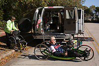 Morehead City, NC -- Paul's wife, Sally, helps ready his bike. Quadriplegic hand cyclist Paul Kelly, 62, trains for the Boston Marathon Tuesday, March 27, 2018. (Justin Cook for The Wall Street Journal)<br /> <br /> SUMMARY:<br /> <br /> Paul Kelly, hand cyclist, Beaufort, NC Training for the Boston Marathon so we would want to shoot in March to run the week before the marathon or marathon Monday, Apriln16. Life as a quadriplegic doesn't keep 62-year-old Paul Kelly on the sidelines. After breaking his neck in a swimming accident in 1978, Kelly was determined to find fitness activities to maintain an active lifestyle. He discovered handcycles while watching his niece compete in the 2006 Marine Corps Marathon and was inspired to start his own marathon career to stay fit. Paul has competed in over 100 half and full marathons. On April 16, he will celebrate his 40th year of living as a quadriplegic by taking on one of the most coveted races for a marathoner -- the Boston Marathon. Kelly is among the 60 handcyclists competing in the 2018 Boston Marathon with a qualifying time of 1:26:37. Most of Paul's distance training takes place at Bogue Banks, which includes Atlantic Beach, Salter Path, and Emerald Isle, N.C. It's Nicholas Sparks worthy scenery with its marshes, waterways, inlets and small islands. Paul is particularly fond of the approach from Atlantic Beach to Bogue Banks -- it's via the high-rise bridge. In cold weather, Paul has to be mindful of the environment and dress in a manner that insulates his legs while also allowing his upper body to ventilate. Paul chooses to train at times of day when the temperatures are more reasonable. He uses hand warmers in his gloves, on the inside the grips on his handcycle and in the legs of his trousers.