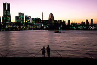 A couple stand at railings on Osanbashi Pier looking at the Yokohama Minato Mirai skyline during a beautiful sunset. Yokohama, Kanagawa, Japan October 17th 2007