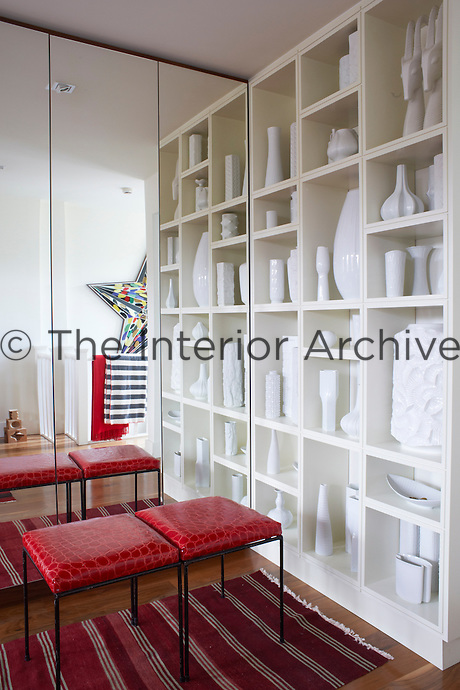 The collection of white ceramics in the bedroom mirrors the black display in the living room,  becoming an artwork in itself