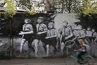 Cyclists passing a wall painted with a mural of Nazi Youth marching, on Stralauer Platz, Berlin, Germany. Picture by Manuel Cohen