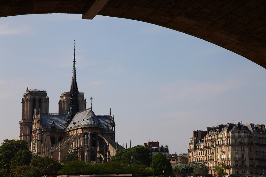 Under a bridge along the Seine river in Paris: An artistic view of the back of the church of Notre Dame, with some surrounding typical buildings. Digitally Improved Photo.