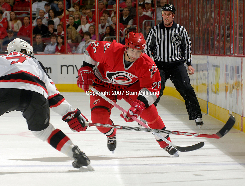 Carolina Hurricanes' Erik Cole skates up ice against the defense of the New Jersey Devils' Paul Martin Thursday, March 15, 2007 at the RBC Center in Raleigh, NC. New Jersey won 3-2.