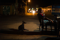 Chucho, a local fisherman, tourist guide and handiman awaits an evening drink at an outdoor bar in Adícora on Venezuela's Paraguaná Peninsula, Dec. 11, 2015. The remote desert peninsula in the Caribbean Sea lays bare the effects of Venezuela's politicized economy after 17 years under Hugo Chavez and successor Nicolas Maduro.
