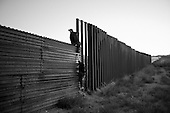 Agua Prieta..Mexico..October 22, 2006....A young Mexican man and woman jump over the border fence to enter the USA illegally in the very early morning hours as they enter into the city of Douglas.....