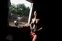 Marshall, 32 years old, takes a break while lifting weights in his neighborhood improvised gym in Monrovia, Liberia on Tuesday  March 20 2007. .Marshall, Nimley and the other men working out are all unemployed. they spend their days at the gym to fight chronic depression..