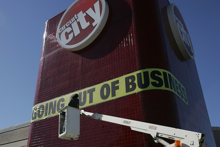 """Reflect Signs worker Rafael Olmedo puts a """"going out of business""""  banner on a Circuit City on Victory Blvd. in the Van Nuys neighborhood of Los Angeles, California  January 29, 2009. Circuit City recently declared bankrupcy and is closing its stores..GERARD BURKHART PHOTO 818-207-0273.."""