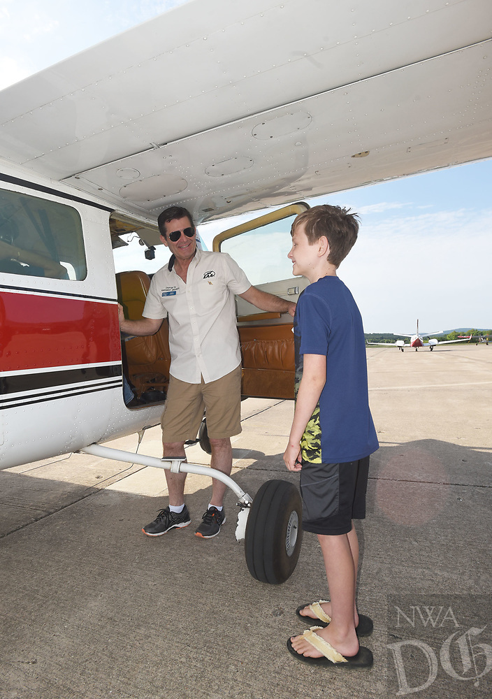 NWA Democrat-Gazette/FLIP PUTTHOFF <br /> FIRST FLIGHT<br /> Pilot Mark Hutton welcomes Ethan Scherrey, 11, into his airplane on Saturday June 9 2018 during the Young Eagles aviation event at Fayetteville Executive Airport. The trip was Ethan's first flight. Members of the Experimental Aircraft Association host Young Eagles events to introduce youngsters to flying and perhaps a career in aviation. Kids learn the basics of flight in a classroom session then get a free airplane ride, said Russ Smith with the association. Pilots volunteer their time and aircraft for the events, he said.