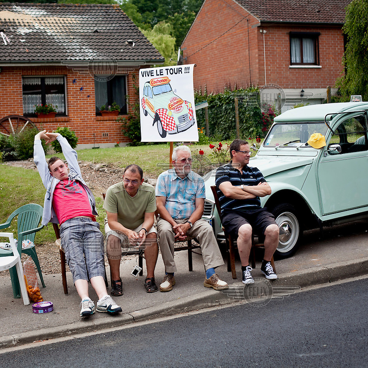 Spectators on the roadside await the riders of the Tour de France to pass by.