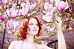 Redhead reaching out to pink magnolias
