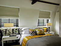 A guest bedroom is situated under the eaves and is decorated in a colour scheme of yellow, black, white and grey