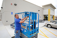 NWA Democrat-Gazette/DAVID GOTTSCHALK Wes Netherton, with Progressive Technologies Inc. of Rogers, prepares a lift Tuesday, August 4, 2015 at Starr Scholar Center the new location of the Fayetteville campus of Hass Hall. Classes begin Thursday at the new location, that has 20 classrooms and office spaces, on Front Street just south of Joyce Boulevard.