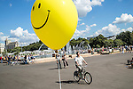 A man rides a bicycle as people stroll in Gorky Park on Saturday, August 17, 2013 in Moscow, Russia.