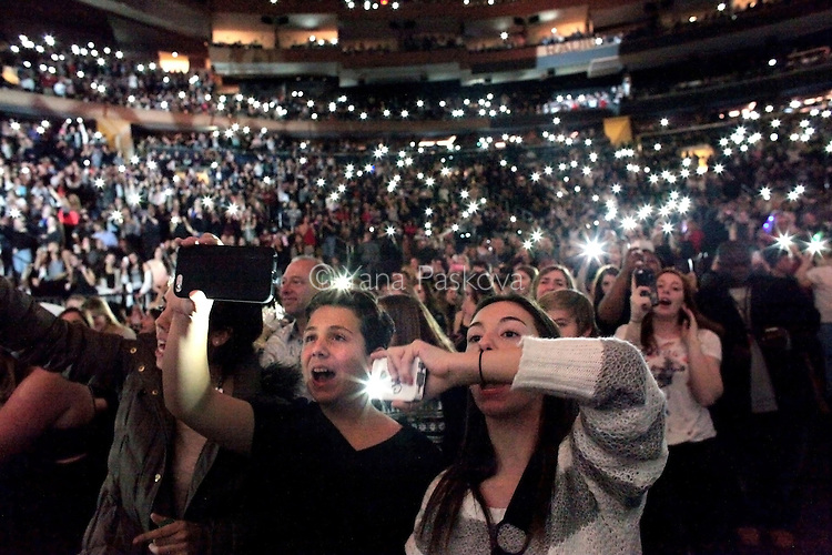 An audience lights up their cell phones instead of lighters, as Sam Smith performs during Jingle Ball at Madison Square Garden in Manhattan, New York on December 12, 2014. The crowd, much like the holiday performance, was energized and sparkling, festive under the glow of reindeer horns, glitter and of course, their cell phones.