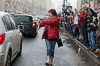 Moscow, Russia, 26/02/2012..An opposition protester hands anti-Putin stickers to passing cars as tens of thousands of people formed a 16-kilometre [10-mile] human chain along Moscow's Garden Ring Road in the latest protest against Prime Minister Vladimir Putin and his presidential election campaign. Opposition activists estimated that they needed 34,000 people to complete the chain and symbolically encircle central Moscow.