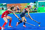 Kathleen Sharkey #24 of United States carries the ball past Giselle Ansley #18 of Great Britain during Great Britain vs USA in a women's Pool B game at the Rio 2016 Olympics at the Olympic Hockey Centre in Rio de Janeiro, Brazil.
