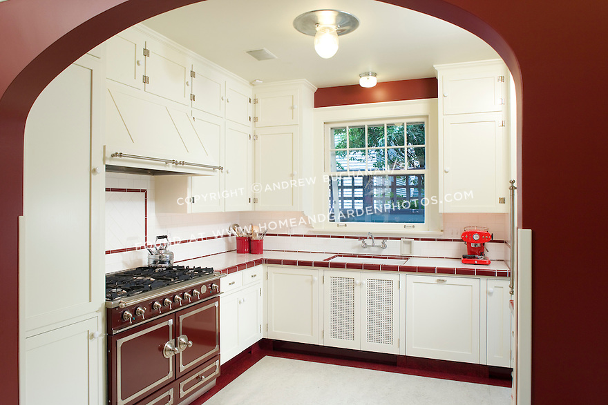 Bold red paint and tile accents contrast the painted white cabinetry in this unusual kitchen. This image is available through an alternate architectural stock image agency, Collinstock located here: http://www.collinstock.com