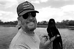 1998-Glen Wilsey holds an injured grackle lakeside by his trailer in Gator Park.  The Florida Everglades are a disappearing world. Overpopulation, the sugar and cattle industry, mismanagement of the land, droughts and bush fires are just a few of the problems the Florida Everglades are facing. Here Glen Wilsey driving his airboat. According to Glen the best thing about being a tour guide in the everglades is driving the airboats. Riding an airboat is fun but driving an airboat is an awesome feeling.