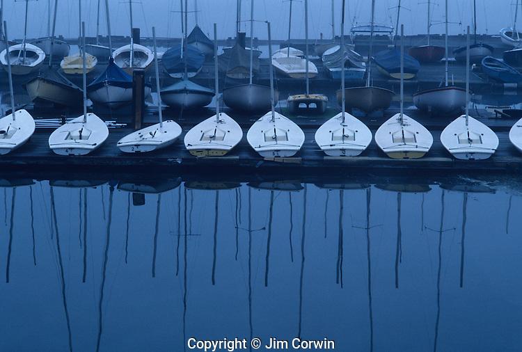 Sunrise over Lake Washington with sailboats lined up on dock in fog Seattle Washington State USA
