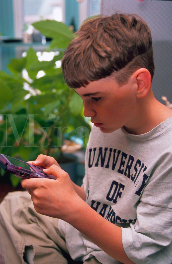 Ten year old boy playing with his Gameboy.
