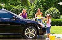 Child and mother and friend having fun at home washiong car together and splashing while laughing