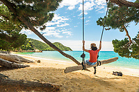Young woman enjoying swing on Anatakapau Bay on Abel Tasman Coast Track, Abel Tasman National Park, Nelson Region, South Island, New Zealand, NZ
