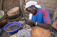 Farmer repairing calabash with fibers of  Burassus aethiopum
